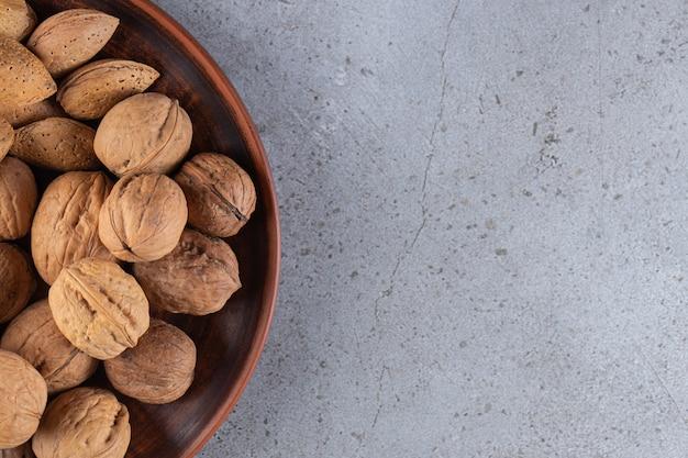 Nozes frescas e saudáveis colocadas sobre uma mesa de pedra.