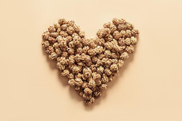 Nozes frescas sem casca em forma de coração conceito de nozes como alimento saudável para o coração