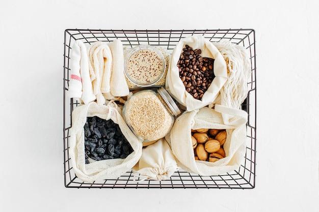 Nozes, frutas secas e sêmolas em sacos de algodão ecológico e potes de vidro em cesto de metal preto. compra de alimentos com desperdício zero. vida livre de resíduos