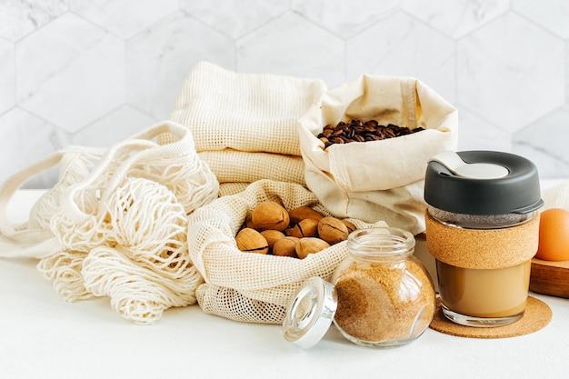 Nozes, frutas secas e sêmolas em sacos de algodão ecológico e potes de vidro na mesa branca da cozinha. compra de alimentos com desperdício zero. vida livre de resíduos