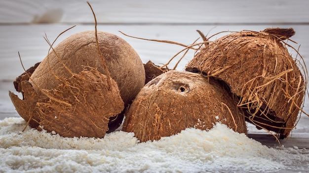 Nozes inteiras de coco espalhadas aparas de fundo de madeira