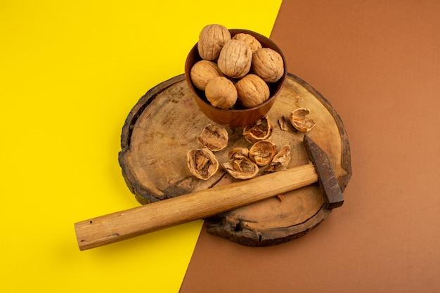 Nozes marrons inteiras e descascadas na mesa de madeira e marrom-amarelo