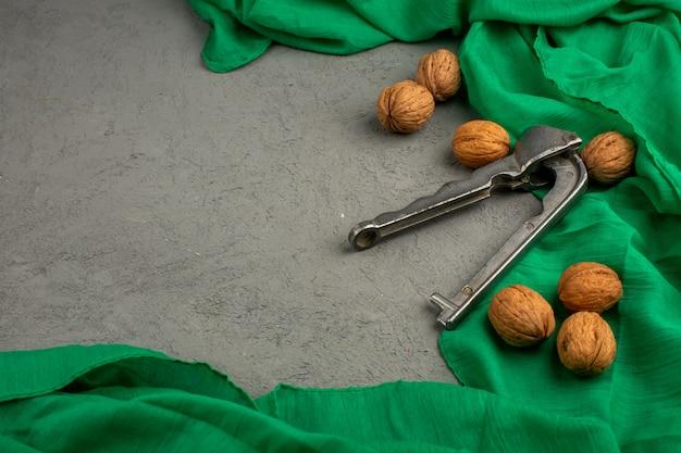 Nozes marrons inteiras em um tecido verde e piso cinza