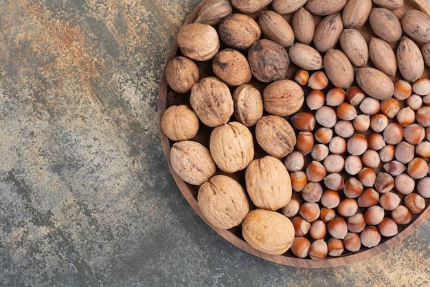 Nozes marrons mistas nutritivas na tigela de madeira. foto de alta qualidade