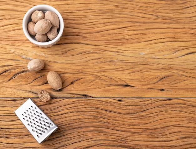 Nozes-moscadas com ralador sobre mesa de madeira com espaço de cópia.
