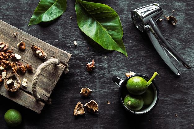 Nozes na mesa escura vintage. comida saudável. as nozes estão espalhadas em uma placa de corte. mesa vintage velha e folhas da noz.