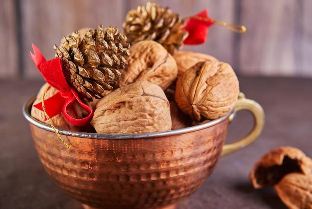 Nozes numa taça de lata, inteiras e picadas, junto ao recheio e às cascas. apresentado em composição de ano novo com cones de abeto