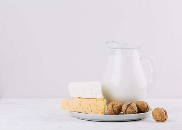 Nozes; pote de leite e queijo no pano de fundo branco