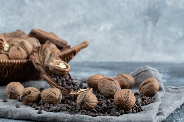 Nozes saudáveis com grãos de café de aroma em uma toalha de mesa cinza.