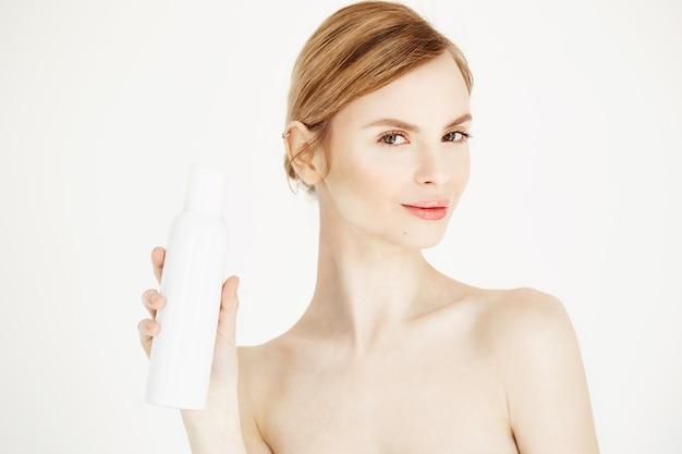 Nude linda loira com pele perfeita fresca, sorrindo segurando o frasco de spray de cosmetologia.