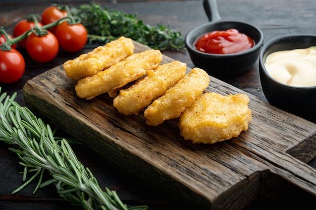 Nuggets à milanesa na mesa de madeira escura.