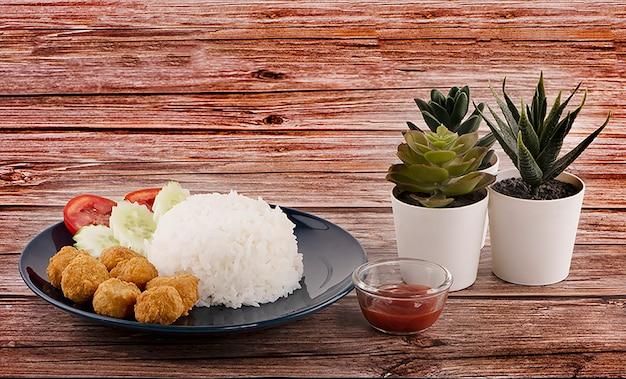 Nuggets de frango com arroz e molho de tomate ao lado de cacto