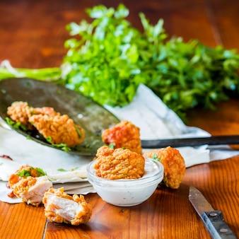 Nuggets de frango com molho de alho na mesa de madeira