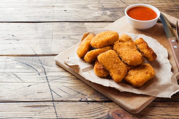 Nuggets de frango com molho de tomate na mesa de madeira. copie o espaço
