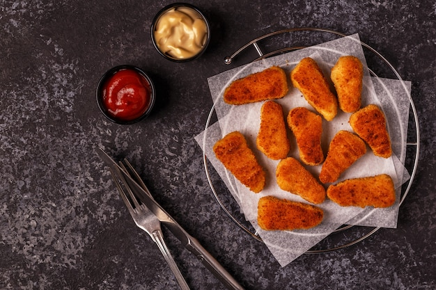 Nuggets de frango com molhos em superfície escura