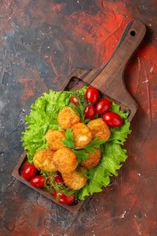 Nuggets de frango com tomate cereja e alface em uma placa de madeira na mesa escura