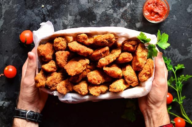 Nuggets de frango com uma crosta crocante. mãos no quadro. mãos e comida. um homem segura uma cesta de pepitas.