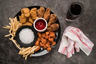 Nuggets de frango; coxa de frango frito; pipoca de frango crocante; batatas fritas com refrigerante e guardanapo em fundo de concreto