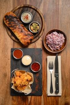 Nuggets de frango crocante frito com três molhos populares para escolha e salada em uma mesa de madeira