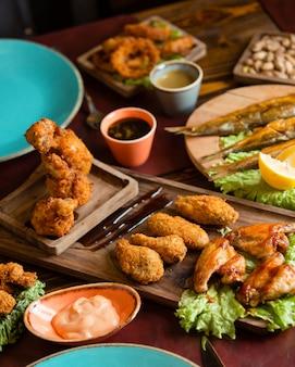 Nuggets de frango crocantes e churrasco com molhos e ervas em uma bandeja de madeira com pratos azuis ao redor.