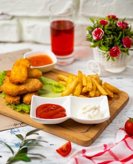 Nuggets de frango e batatas fritas, molhos de ketchup e maionese em uma cozinha