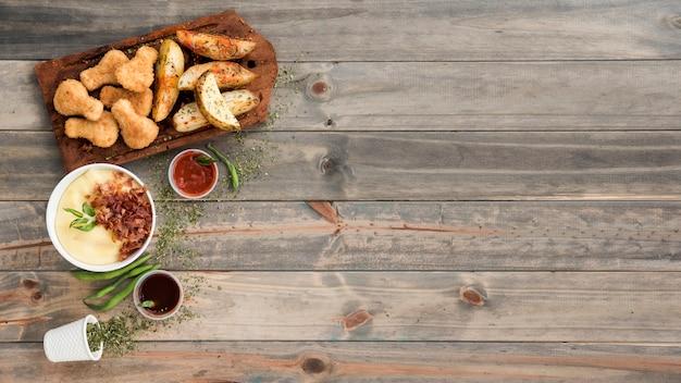Nuggets de frango e fatias de batata na tábua de madeira