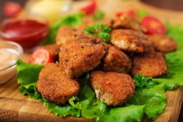 Nuggets de frango e molho em uma mesa de madeira