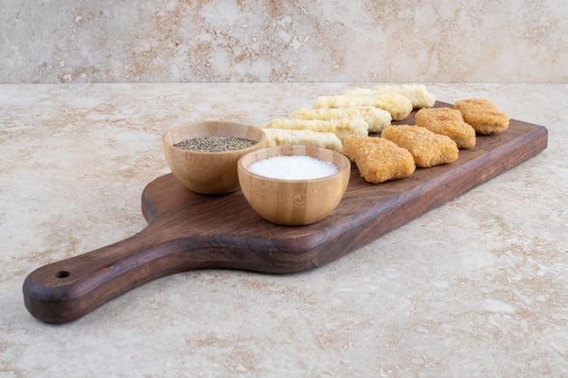 Nuggets de frango e palitos de queijo em uma placa de madeira com vários molhos ao redor.