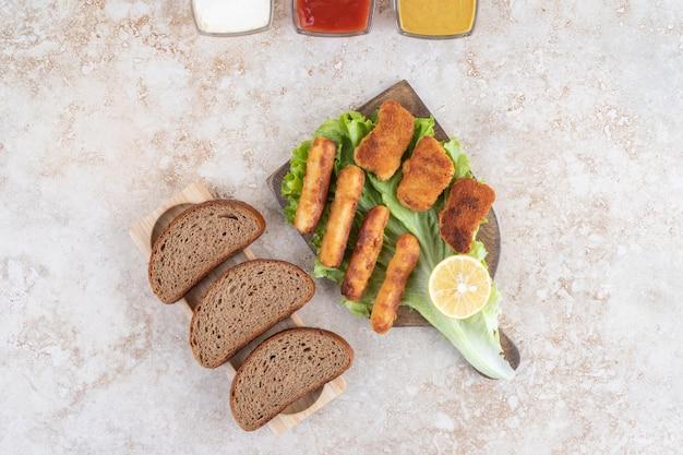 Nuggets de frango e salsichas fritas em uma folha de alface verde em uma placa de madeira.