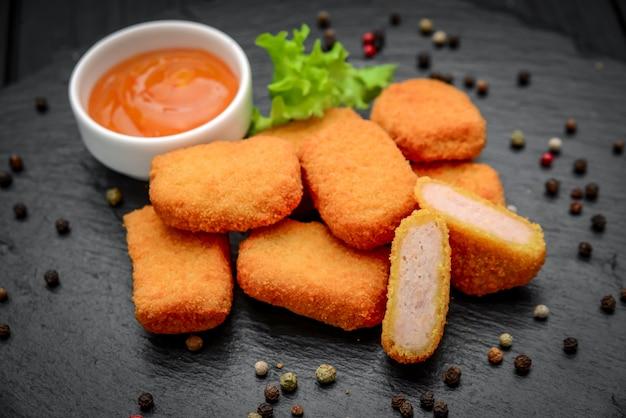 Nuggets de frango fast food com ketchup, contra uma superfície escura