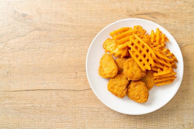 Nuggets de frango frito com batatas fritas no prato
