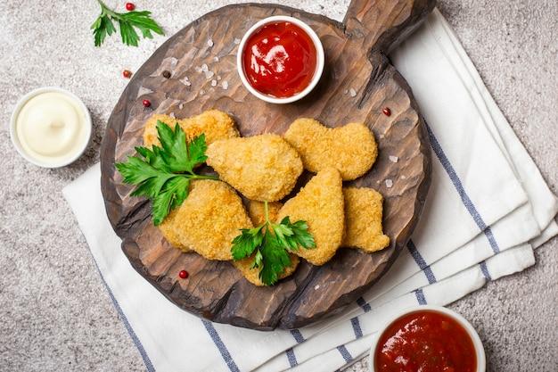 Nuggets de frango frito crocante com close up de molhos populares