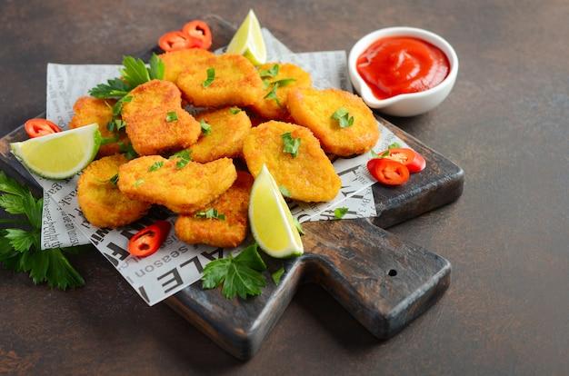 Nuggets de frango frito crocante com molho de tomate no fundo escuro