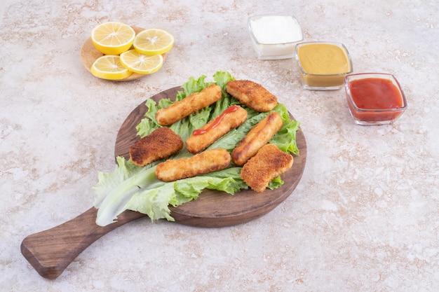 Nuggets de frango frito e palitos de linguiça grelhada em um pedaço de alface com molhos ao redor.