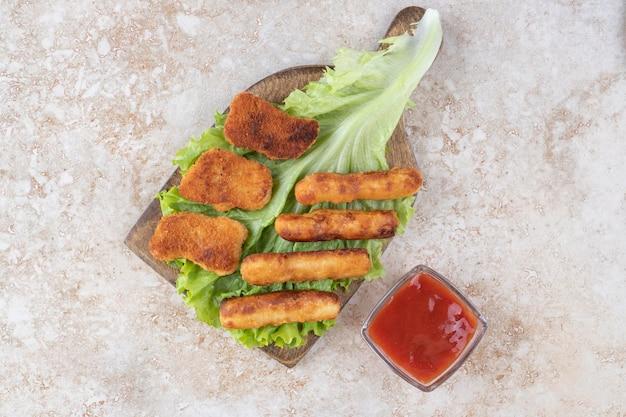 Nuggets de frango frito e palitos de linguiça grelhada em um pedaço de alface servido com ketchup.