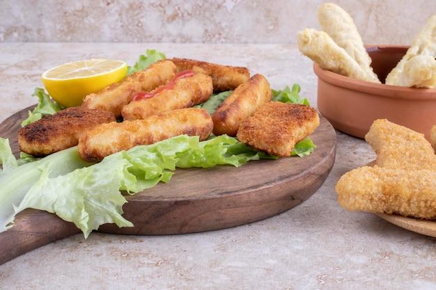 Nuggets de frango frito e palitos de queijo em uma placa de madeira em um pedaço de folha de alface.