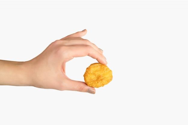 Nuggets de frango frito na mão feminina em fundo branco