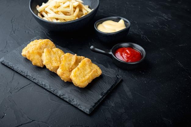 Nuggets de frango frito na mesa preta.