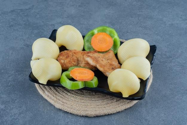 Nuggets de frango grelhado e batatas cozidas na chapa preta.