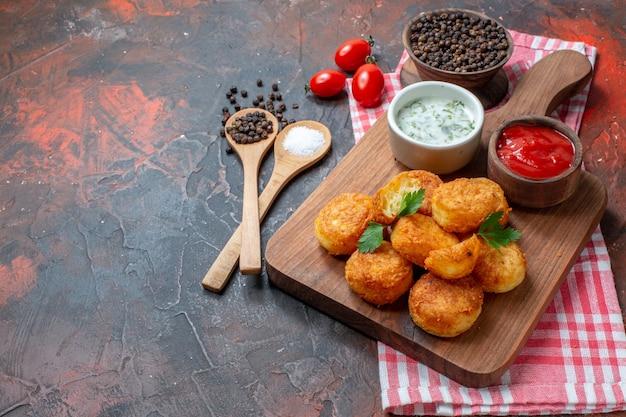 Nuggets de frango na placa de madeira com molhos, tomate cereja, colheres de pau pimenta preta em uma tigela na mesa escura.