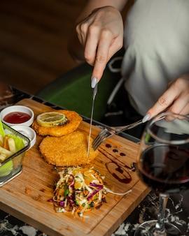 Nuggets de frango redondo em uma placa de madeira com sala e copo de vinho tinto.