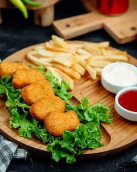 Nuggets de frango servidos com batata frita, ketchup e maionese