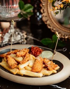 Nuggets de frango servidos com batatas fritas e molhos