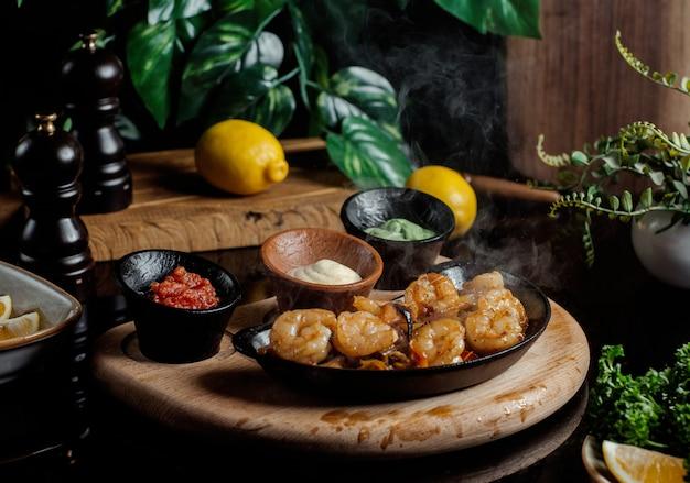 Nuggets de frango servidos com molho pesto, creme e tomate em cerâmica preta