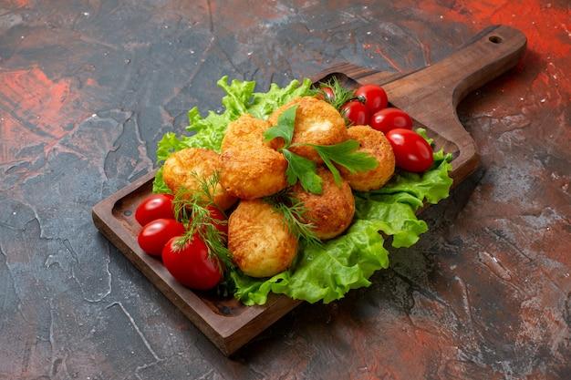 Nuggets de frango, tomate cereja, alface, vista inferior, numa tábua, na mesa escura, com espaço de cópia