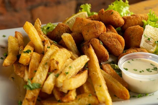 Nuggets de peixe com batatas fritas e molho.