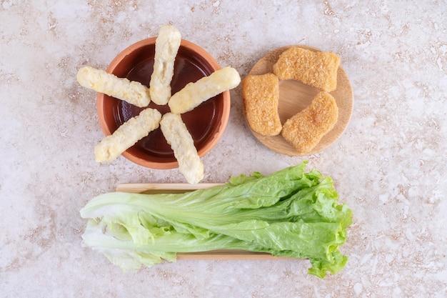 Nuggets, palitos de queijo e folhas de alface no chão.
