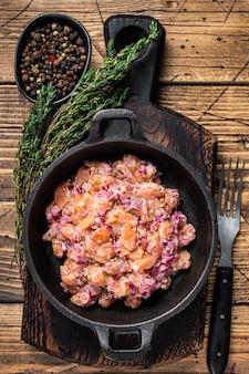 Numa frigideira tártaro ou tártaro com salmão, cebola roxa, rúcula e alcaparras. mesa de madeira. vista do topo.