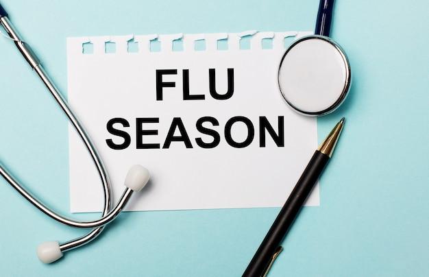 Numa parede azul clara, um estetoscópio, uma caneta e uma folha de papel com a inscrição temporada gripe. conceito médico