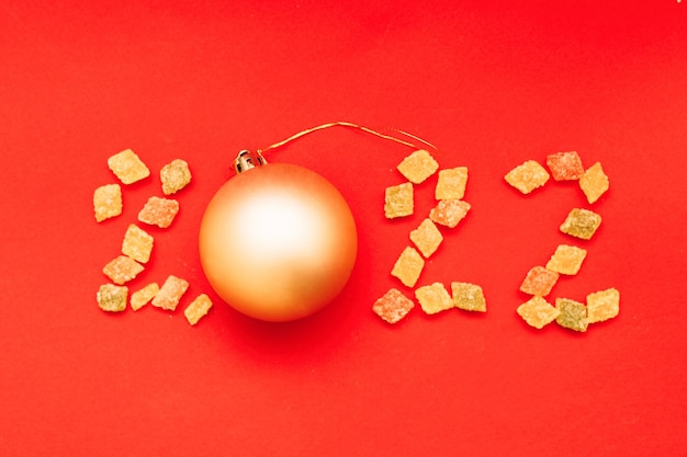 Numeral 2022 de doces multicoloridos e bola de natal dourada em fundo vermelho
